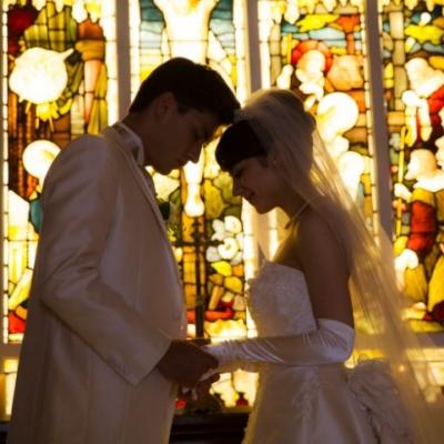ステンドグラスの前で結婚を誓う新郎新婦