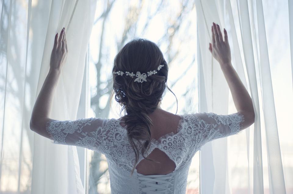 カーテンnを開けるウェディングドレスを着た新婦