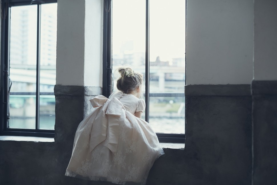 窓の外を眺めるドレスを着た子ども