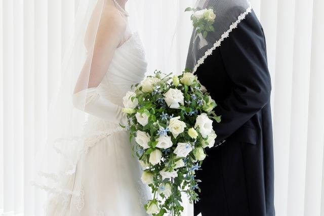 結婚式でウェディングドレスとタキシードを着た新郎新婦
