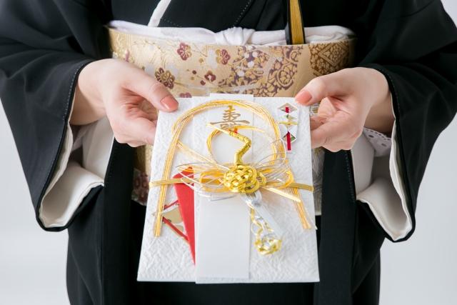 結婚式のご祝儀を渡す女性