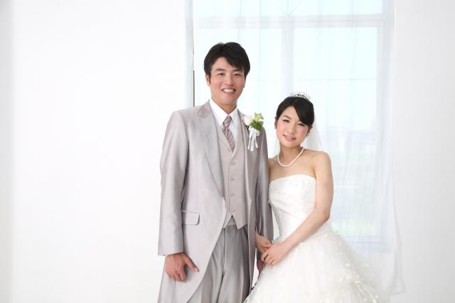 低身長の花嫁さんとともに微笑む花婿さん